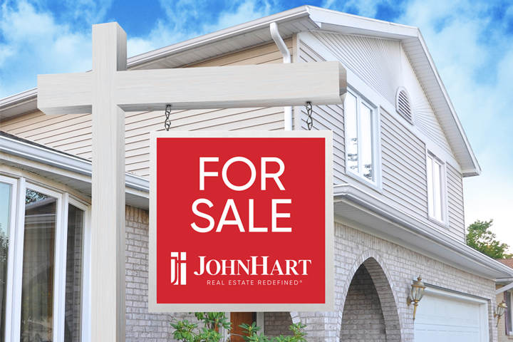 JohnHart for sale sign in front of a white house